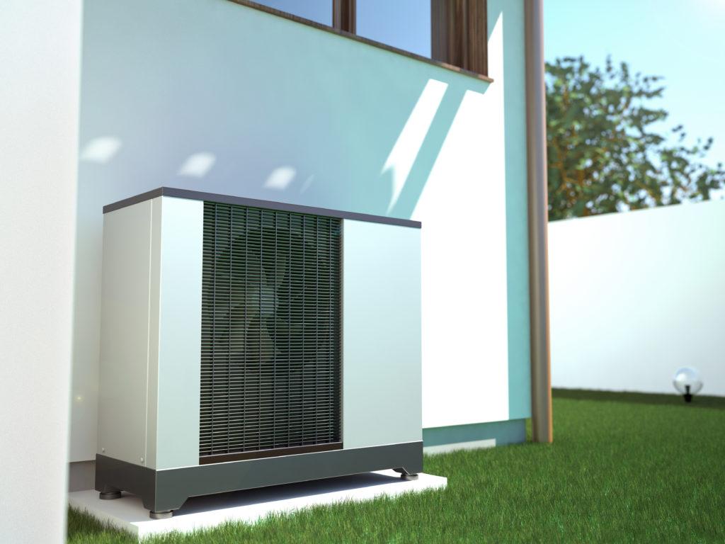 Luft-Wasser-Wärmepumpe an einem weißen Einfamiilenhaus mit kurzem grünen Rasen.