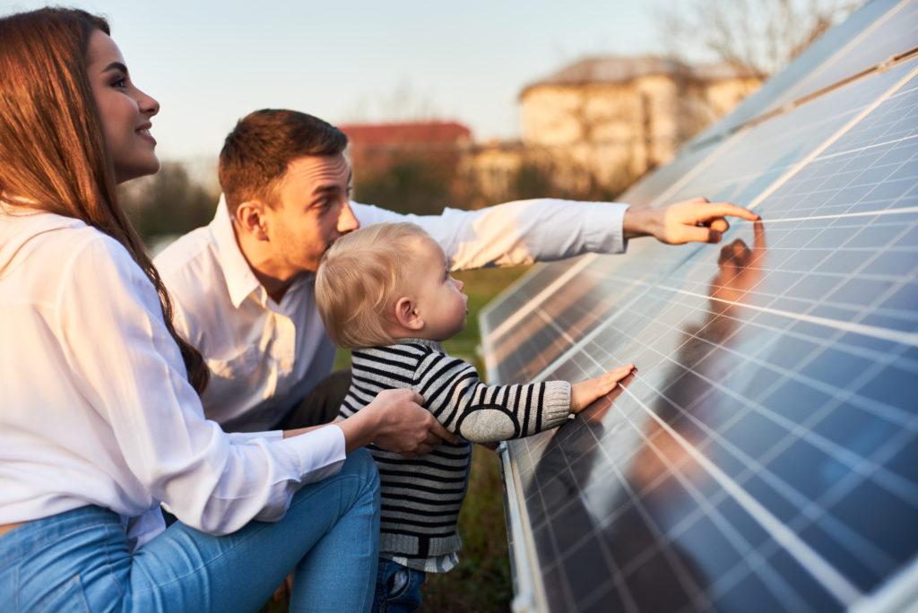 Junges Paar mit Kleinkind, das zusammen mit dem jungen Mann die Hand auf Solarmodule legt.
