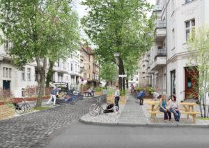 Begrünte Straße in einer Stadt, Menschen auf SItzbänken und mit Fahrrädern, ein Mann belädt den Kofferraum eines PKW, viele Bäume, keine Autos