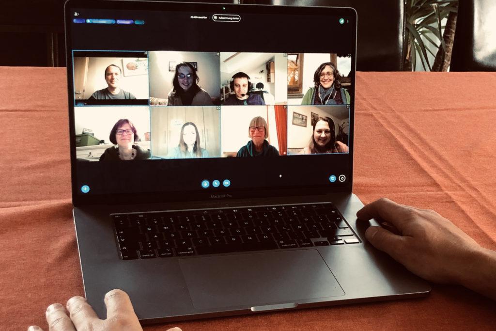 Laptop auf Tisch, auf dem eine Videokonferenz mit 8 Personen zu sehen ist